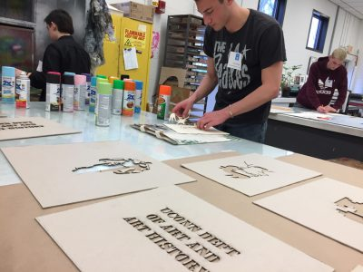 Prospective students making their own stencils and tote bags in the print shop for Spring into the Arts.