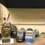 An image of artwork and welding helmets inside the metal shop